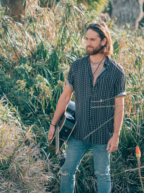 Pensive bearded hipster man walking in jungle with guitar looking at camera