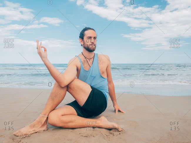 Sportive bearded male training on tranquil seashore and doing yoga asana against blue sea and sky