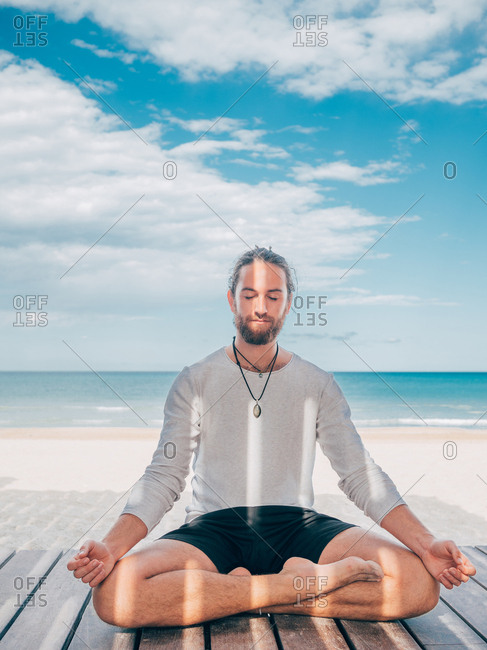 Adult bearded male meditating while sitting in lotus pose on wooden pier by seashore with legs crossed and closed eyes