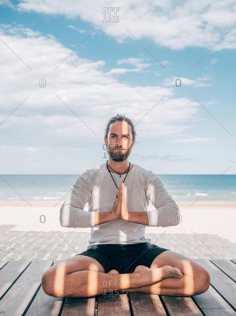 Adult bearded male meditating while sitting in lotus pose on wooden pier by seashore with legs crossed and looking at camera
