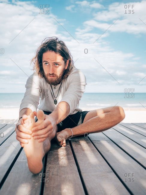 Adult bearded male stretching while sitting on wooden pier by seashore looking away