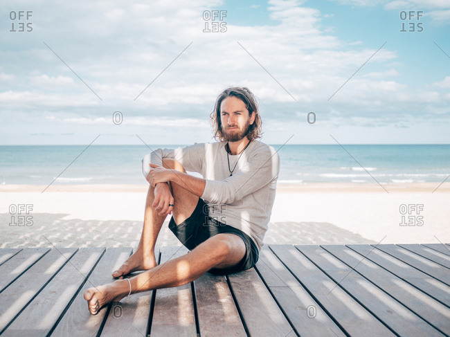 Adult bearded male sitting relaxed resting on wooden pier by seashore looking away