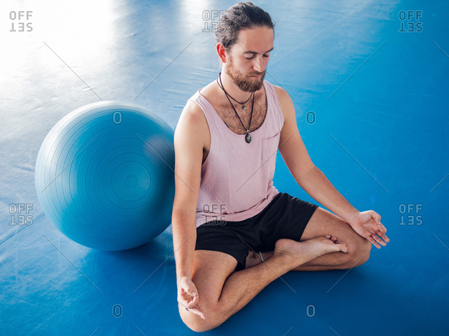 From above of bearded man in sportswear with eyes closed and legs crossed meditating on blue floor with gymnastic balls in studio