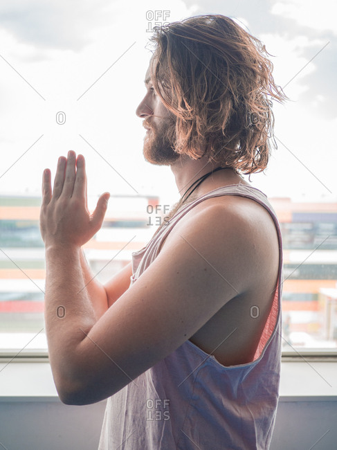 Bearded man in sportswear standing in one leg with prayer hands looking away on blue floor in studio