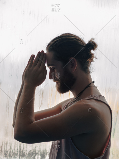 Relaxed thoughtful male in harmony with praying hands in forehead near steamy windows with closed eyes