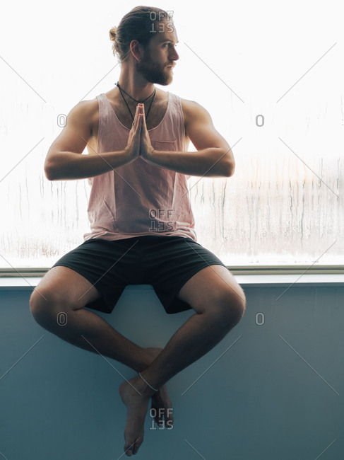 Relaxed thoughtful male sitting in harmony near steamy window and looking away