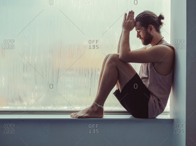 Side view of relaxed thoughtful male sitting in harmony on sill near against steamy window with eyes closed