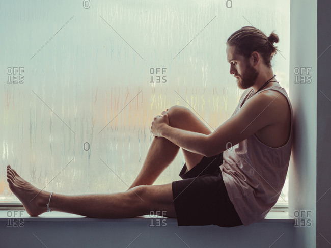 Side view of relaxed thoughtful male sitting in harmony on sill near against steamy window and looking down
