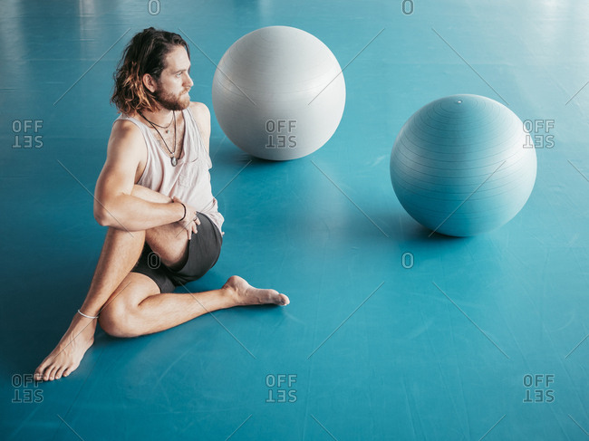 From above of bearded man in sportswear stretching with legs crossed on blue floor with gymnastic balls in studio