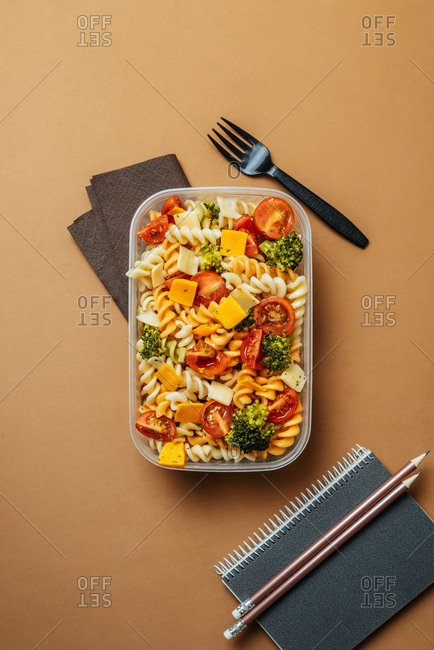 Top view of plastic lunchbox with pasta, tomatoes, cheese and broccoli placed by black plastic fork and notepad with pencils on brown background