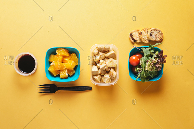 Top view of food containers with bread and tomatoes, arugula and pieces of orange, soy sauce and chicken fillet with black plastic fork on yellow background