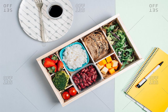 Top view of food box with strawberry and tomatoes, broccoli and beans, rice and brad, cheese and arugula placed on table by yellow copybook with pen and plate with soy sauce