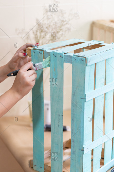 Woman paining wooden box in blue color with brush