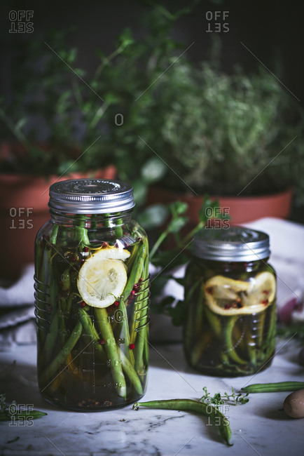 Transparent cylindrical glass container with marinated green beans and flesh lemon arranged on rustic table
