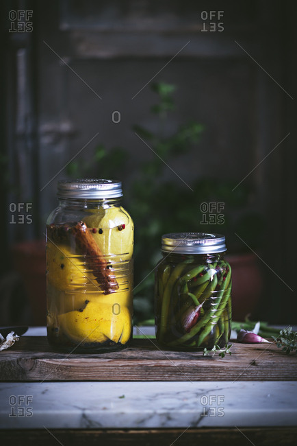 Transparent cylindrical glass container with marinated green beans and yellow fleshy vegetable with cinnamon arranged on rustic table