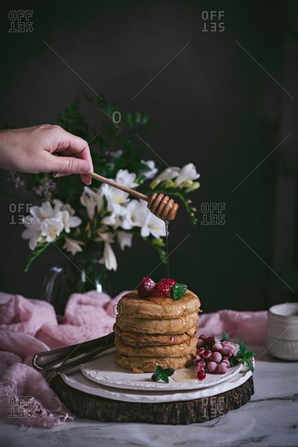 Stack of raspberry pancakes with fresh berry and dripping honey on porcelain plate at marble tabletop text to case with flowers over dark background