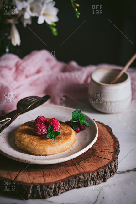 Tasty golden brown pancake topped with fresh raspberry and mint leaves on stylish white plate on marble tabletop