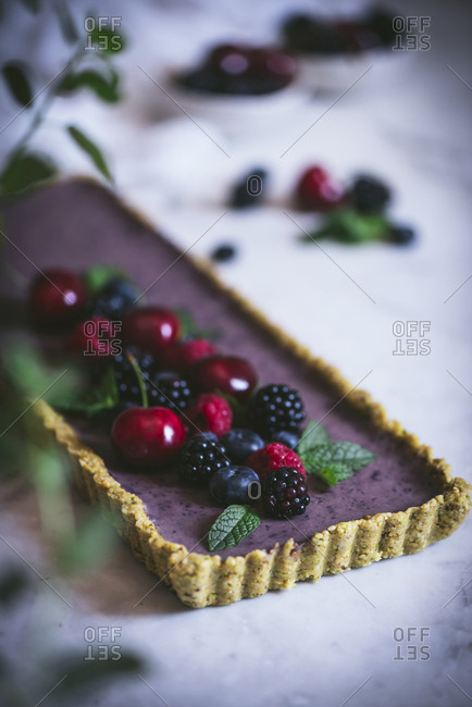 From above ripe tasty cherry blackberry blueberry raspberry with green stems on top of appetizing rectangular cake on white table