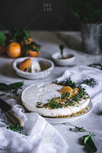 From above tasty appetizing decorated with mandarin green and nuts tangerine cake and whole citruses knife bowl with spoon on table