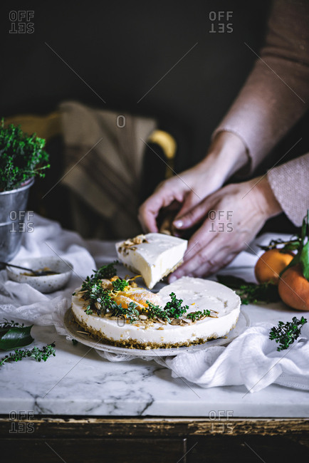 White creamy tasty tangerine cake decorated with green and citrus on table cutting by cook hands