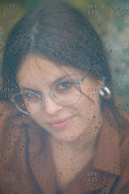 Portrait of beautiful woman with glasses looking out of wet window on rainy day looking at camera