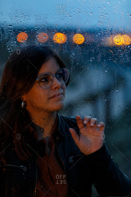 Portrait of beautiful woman with glasses looking out of wet window on rainy day looking away