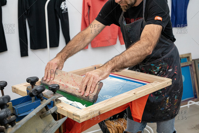 Crop man in dirty apron working with silkscreen while creating print on t-shirt in workshop
