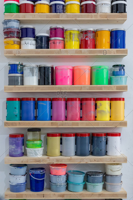 Shelves with colorful tins of paint of different shape size and color at workplace