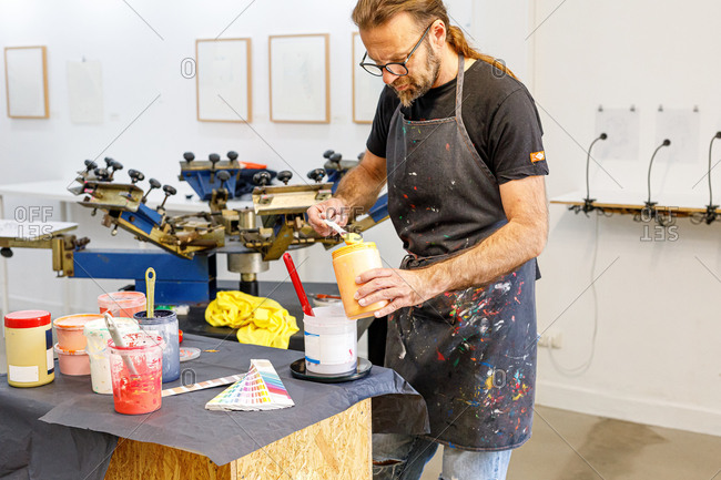 Concentrated man with long hair and glasses wearing dirty apron mixing various paints for serigraphy in workshop