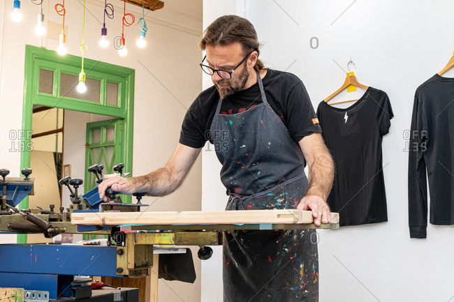 Concentrated male artist in dirty apron working with silkscreen while creating print on t-shirts in workshop