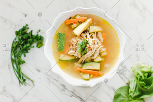 Served bowl of chicken soup with carrot, coriander and zucchini on table