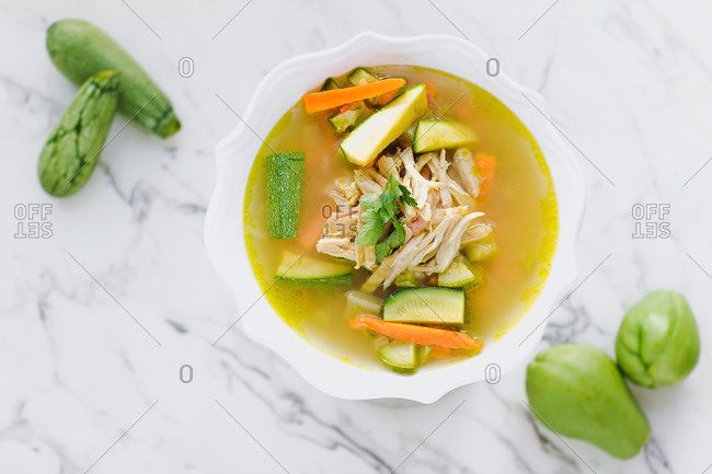 Served bowl of chicken soup with carrot and zucchini on table with zucchini and cutting board