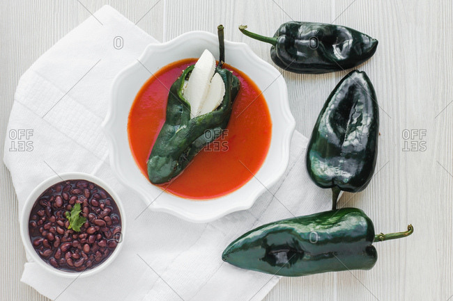 Bowl with served pepper stuffed with mozzarella in gazpacho on table with bowl of beans and pepper on cutting board