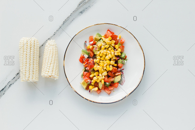 Served bowl with corn and cut tomatoes and zucchinis on table with tomatoes and corn