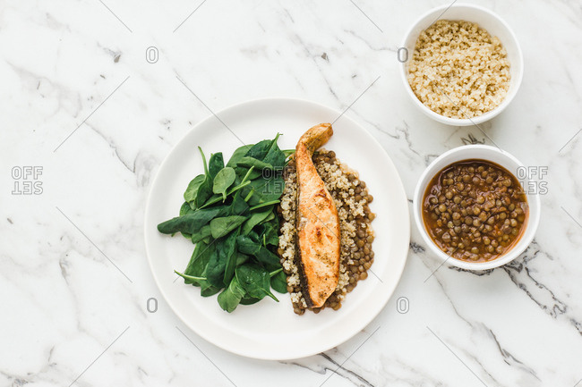 Served plate with salmon steak couscous beans and greenery on table with bowls of beans and couscous