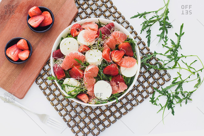 Top view of bowls with strawberry, grapefruit and rocket salad on table served on kitchen boards