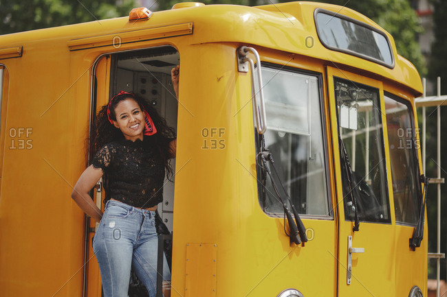 Young cheerful beautiful black woman standing on yellow train in drivers cabin in berlin looking at camera