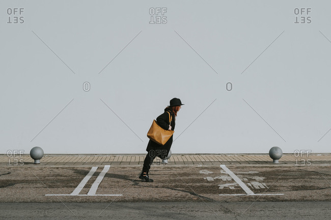 Side view of stylish woman in black clothes bending forward catching balance on street against white wall