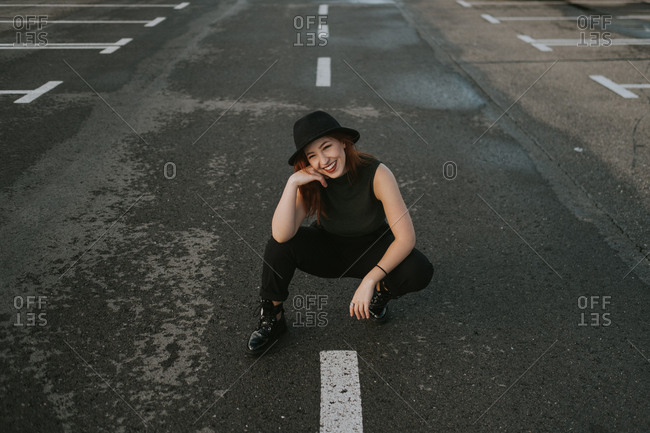 From above attractive young woman with red hair in black hat smiling and sitting on road with white stripes markup