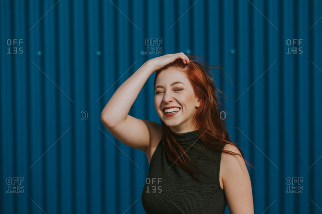 Smiling woman squinting in sun and enjoying weather