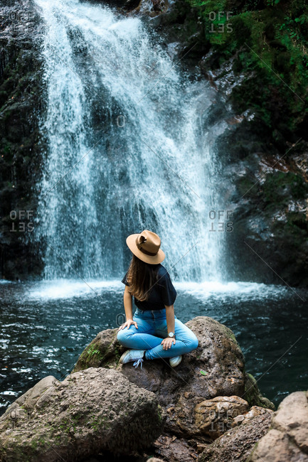 Cheerful female traveler in hat smiling and looking at camera while sitting on wet boulder near waterfall