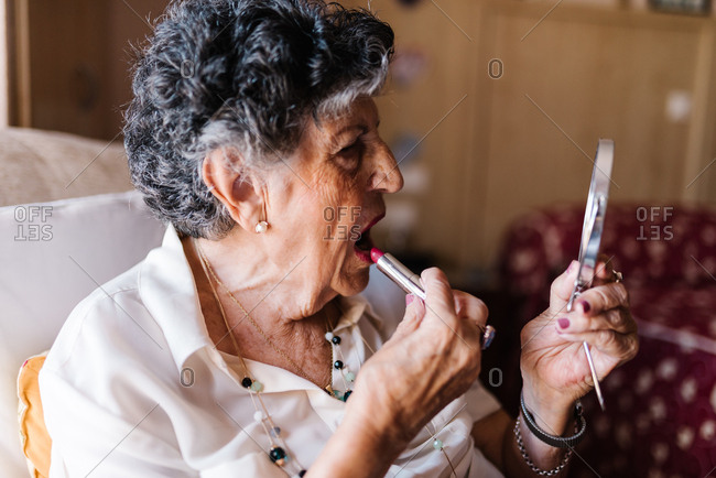 Aged gray haired female applying lipstick while looking in mirror and sitting on armchair at home