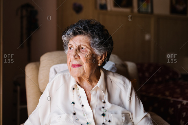 Portrait of happy senior curly gray haired woman in white shirt and with beads on neck looking away at home