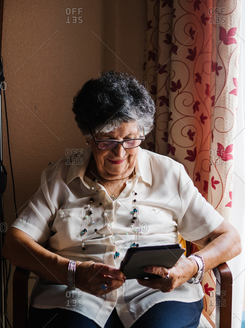 Elderly gray haired woman in shirt and glasses sitting on armchair and reading e-book in apartment