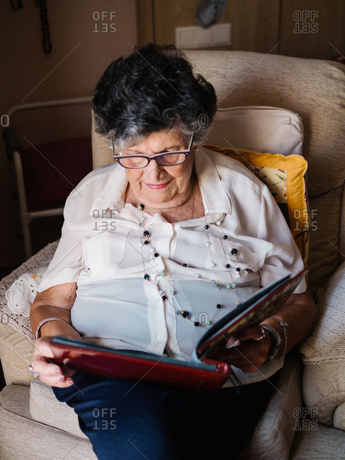 From above of gray haired woman in glasses looking at photo of granddaughter in album at home
