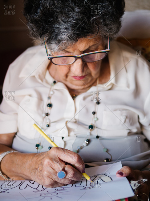Senior gray haired female in white shirt and glasses drawing on paper with pencil sitting on armchair at home