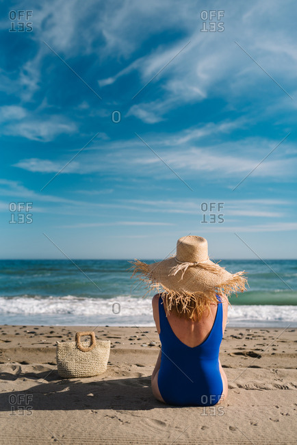 Back view of pretty woman in hat with fringe at edge and dark blue swimsuit sitting with bag on sandy seaside looking at foam waves under turquoise cloudy sky