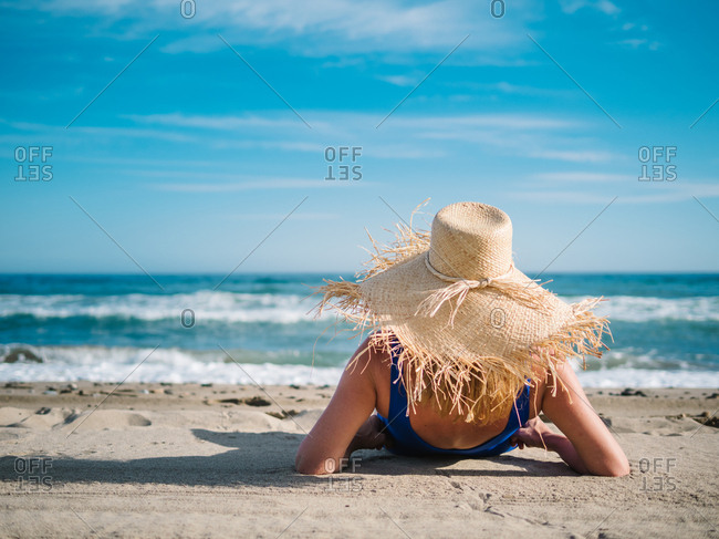 Back view of pretty woman in hat with fringe at edge and dark blue swimsuit on sandy seaside looking at foam waves under turquoise cloudy sky