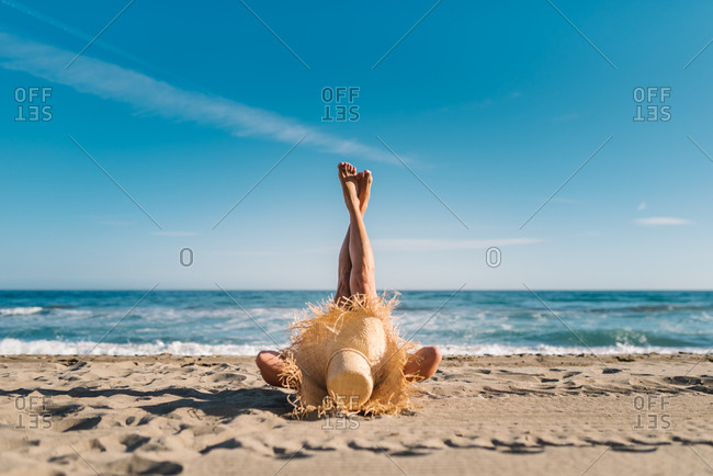 Relaxed woman enjoying good weather lying with raised crossed legs up on sandy beach in bright day