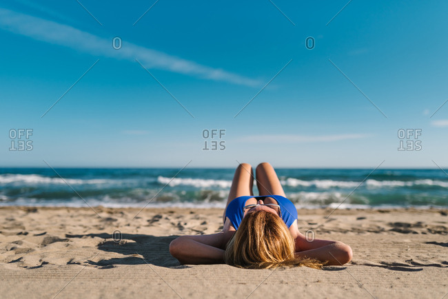 Relaxed woman enjoying good weather lying down on sandy beach in bright day